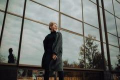 fille à côté des fenêtres modernes de miroir construisant en manteau et verres image stock