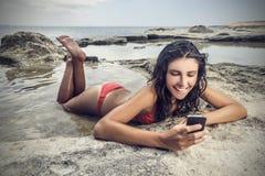 Fille à l'aide d'un téléphone à la plage Image stock