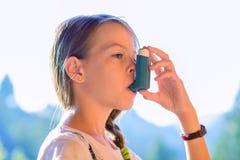 Fille à l'aide de l'inhalateur d'asthme dans un parc photos stock