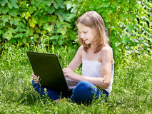 Fille à l'aide de l'ordinateur portable sur l'herbe Photographie stock