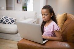 Fille à l'aide de l'ordinateur portable tout en se reposant sur le sofa photos libres de droits
