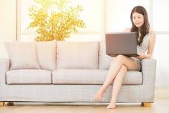 Fille à l'aide de l'ordinateur sur le bureau de sofa à la maison Image libre de droits