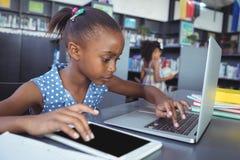 Fille à l'aide de la tablette et de l'ordinateur portable dans la bibliothèque photographie stock
