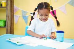 Fille à l'aide de ses doigts pour peindre Images libres de droits