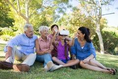 Fille à l'aide du casque de vr tout en se reposant avec sa famille Images libres de droits