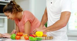 Fille à l'aide du comprimé numérique avec la mère tandis que légumes de coupe de père dans la cuisine banque de vidéos