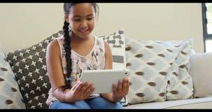Fille à l'aide du comprimé numérique dans le salon 4k banque de vidéos