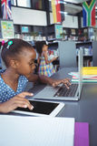 Fille à l'aide du comprimé numérique et de l'ordinateur portable dans la bibliothèque photo stock