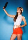 Fille à l'aide du comprimé prenant la photo d'elle-même image libre de droits