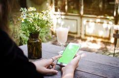 Fille à l'aide du téléphone intelligent en café, style de vintage Photos stock