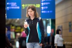 Fille à l'aide du téléphone portable dans l'aéroport Photos libres de droits