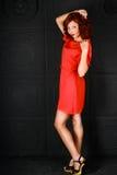 Fille à l'arrière-plan rouge de noir de robe Photos stock