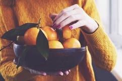Fille à la maison tenant la cuvette avec des mandarines d'hiver Photos stock
