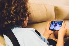 Fille à la maison utilisant son smartphone Photographie stock libre de droits