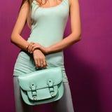 Fille à la mode avec un sac de turquoise sur le fond pourpre Photographie stock libre de droits