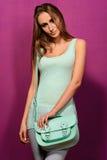 Fille à la mode avec un sac de turquoise sur le fond pourpre Photos libres de droits