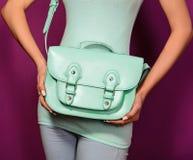 Fille à la mode avec un sac de turquoise sur le fond pourpre Photo stock