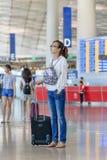 Fille à la mode regardant l'information de vol l'aéroport international capital de Pékin Photo stock