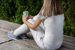Fille à la mode s'asseyant sur le banc avec le pantalon rayé et tenant la tasse de café Femme se reposant en parc sur le temps be images stock