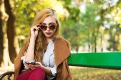 Fille à la mode s'asseyant sur un banc de parc Photographie stock