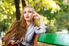 Fille à la mode s'asseyant sur un banc de parc Images libres de droits