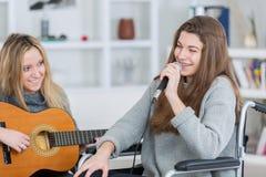 Fille à la mode sur le fauteuil roulant chantant avec l'ami Photos libres de droits