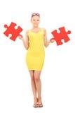 Fille à la mode tenant deux morceaux d'un puzzle Photographie stock libre de droits