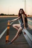 Fille à la mode urbaine avec le longboard posant dehors sur la route au coucher du soleil Photos libres de droits