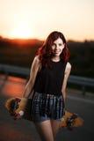 Fille à la mode urbaine avec le longboard posant dehors sur la route au coucher du soleil Image stock