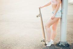 Fille à la mode urbaine avec le longboard posant dehors sur la route au coucher du soleil Image libre de droits