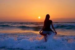 Fille à la vague de mer sur le coucher du soleil Photographie stock libre de droits