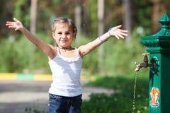 Fille éclaboussant l'eau au parc Images stock
