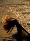 Fille éclaboussant l'eau de mer Photographie stock libre de droits