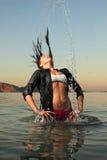 Fille éclaboussant l'eau de mer de son cheveu Image libre de droits