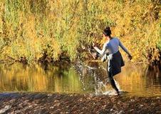 Fille éclaboussant l'eau sur le déversoir Photos libres de droits
