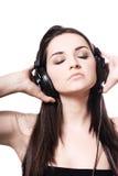 Fille écoutant des écouteurs Photographie stock libre de droits