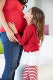 Fille écoutant l'estomac de la mère enceinte photo stock