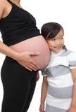 Fille écoutant la grossesse de chéri Images stock