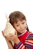 Fille écoutant la mer par un seashell images libres de droits
