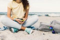 Fille écoutant la musique avec des écouteurs sur la plage Image stock