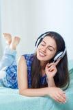 Fille écoutant la musique dans des écouteurs à la maison images libres de droits