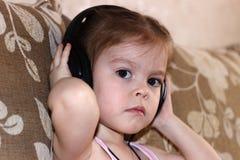 Fille écoutant la musique sur des écouteurs Image stock