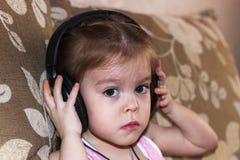 Fille écoutant la musique sur des écouteurs Image libre de droits