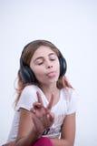 Fille écoutant une musique sur l'écouteur faisant un signe de la paix et de l'amour Image libre de droits