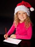 Fille écrivant une lettre au père noël Photographie stock libre de droits