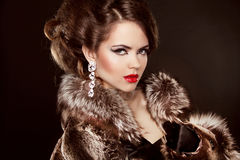 Fille élégante à la mode dans le manteau de fourrure de luxe. Lèvres rouges. Coiffure Images libres de droits