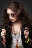 Fille élégante assez jeune dans la veste en cuir et des lunettes de soleil noires Photographie stock libre de droits