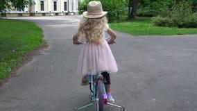 Fille élégante d'enfant avec le chapeau et la robe rose montant un vélo dans extérieur banque de vidéos