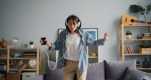 Fille élégante dans des écouteurs dansant écouter le smartphone de participation de musique banque de vidéos