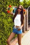 Fille élégante dans des poses de lunettes de soleil avec le longboard Photo stock